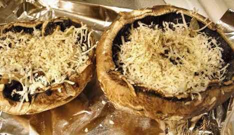 Portobello mushrooms ready to broil with herbs, garlic and mozzarella