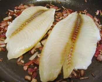 Tilapia fillets frying, skin side up